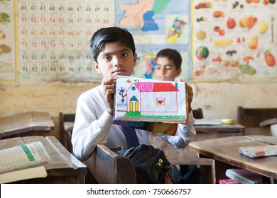 Boy displaying artwork. Thatta, Sindh, Pakistan - September 08 2015. Government Schools Condition.