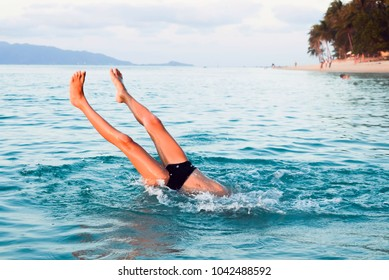 A boy dives into the sea at sunset. Only his feet are visible from the water.