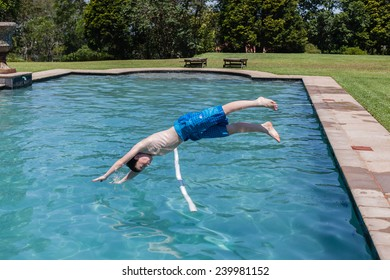 Boy Diving Pool Boy diving into swimming pool water at home summer playtime