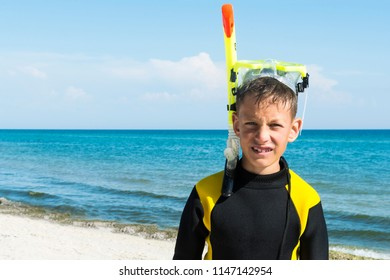 Boy in divingsuit and mask and snorkel at sea background.