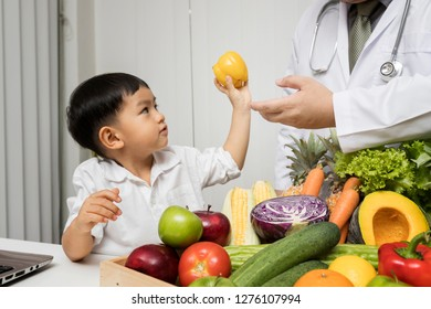 A boy and doctor happy to have healthy food. Kid learning about nutrition with doctor to choose eating fresh fruits and vegetables.