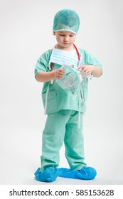 Boy in doctor uniform posing isolated in white