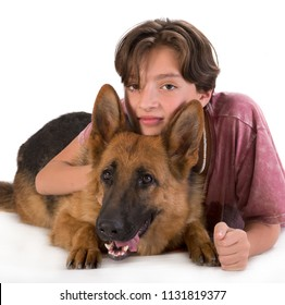 Boy and dog portrait in studio, 11 years old boy hugs German shepherd pup isolated on white background. Looking at the camera.