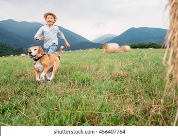 Boy and dog run together on the field with haystacks
