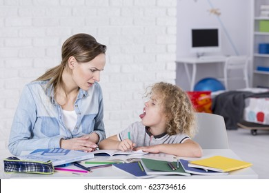 Boy doing homework with mother and sticking tongue at her