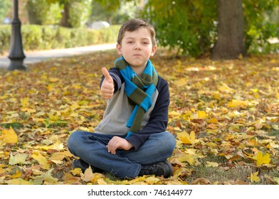 Boy doing meditation exercise sit in the yellow autumn leaves. A long scarf is tied around the boy's neck