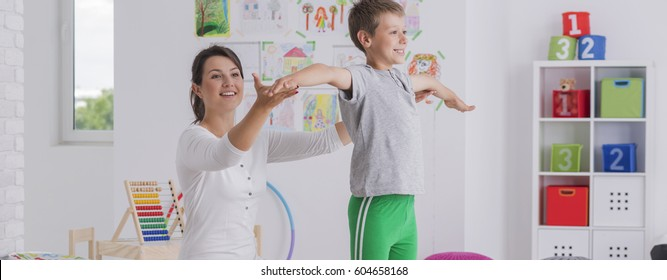 Boy doing physical exercises with his physiotherapist