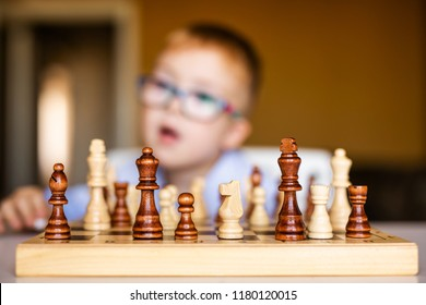 Boy with down syndrome with big glasses playing chess with great interest