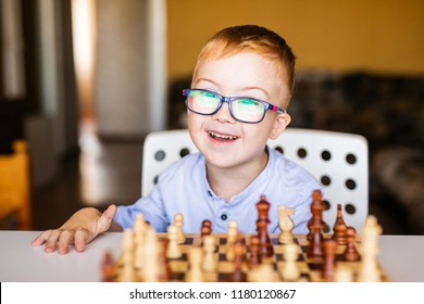 Boy with down syndrome with big glasses playing chess with great interest. Happy smiling boy