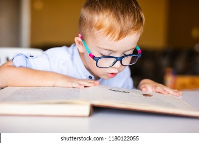 Boy with down syndrome with big glasses reading book