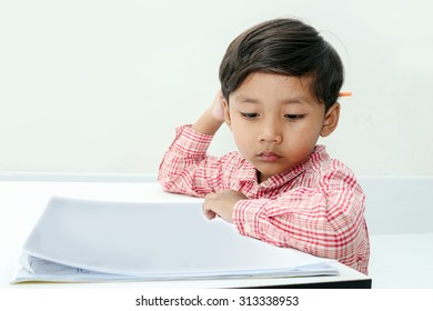 Boy drawing colored pencils in a book on room background.