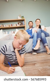 Boy drawing on book while parents looking at him from sofa in living room