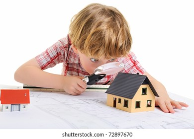 boy drawing and playing with house models on architect's plans