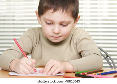 Boy drawing with red pencil sitting at wooden desk
