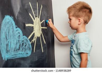 the boy draws chalk