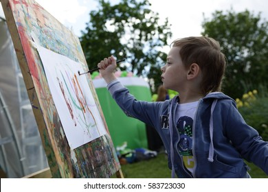 Boy draws paints on the paper in the park