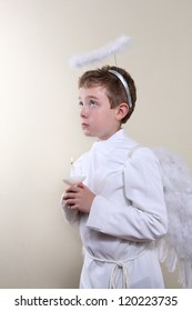 Boy dressed as an angel holding a candle