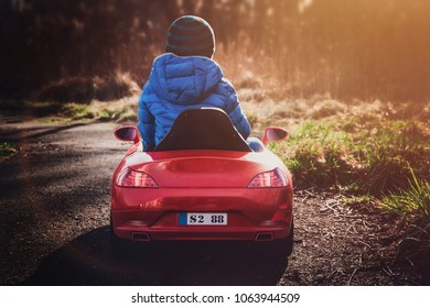 A boy dressed in a blue jacket is driving a red toy car. Fun concept with a child, spending free time, children's day. The boy is playing with dad on a walk. Lifestyle. Boy on sunset background.