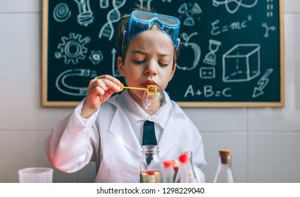 Boy dressed as chemist blowing bubbles in front of a blackboard with drawings