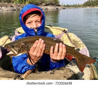 Boy dressed for cold fishing on a lake in a float tube or pontoon, with a large trout fish (Brook Trout hybrid with Lake Trout, called Splake) he caught with a fly rod