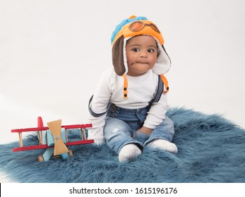 Boy dressed as a pilot with white t-shirt, blue jeans and with a mole on the cheek, with white background in studio