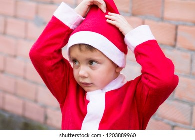 boy dressed as santa clapping his hat