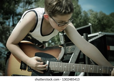 A boy dressed in a tank top and wearing glasses, plays a guitar on stage at an outdoor concert on a bright, sunny day.