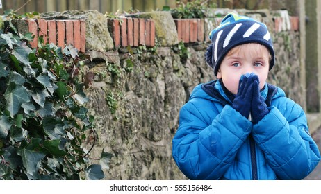 Boy dressed up in winter clothes feeling cold standing in front of a stone wall