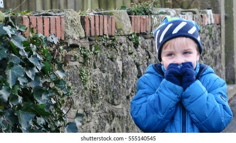 Boy dressed up in winter clothes standing in front of a stone wall smiling mischievously