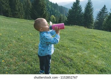 boy drinking from bottle standing on meadow