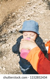 boy drinking from bottle that his mother is holding