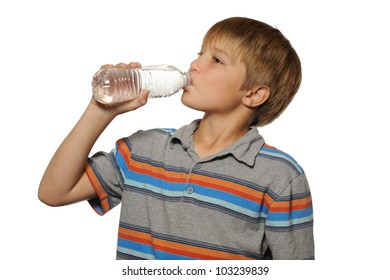 Boy Drinking Bottle of Water. Young boy drinking a bottle of water on white.