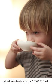 Boy drinking from a dish