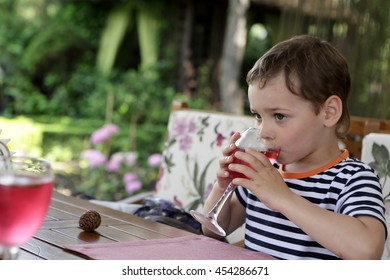 Boy drinking juice at table in cafe