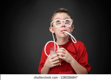 Boy drinking milk through silly straw glasses, while looking up