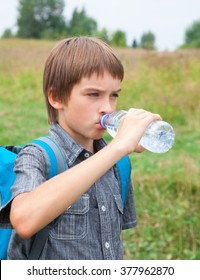 Boy drinking still water from pet bottle outdoors