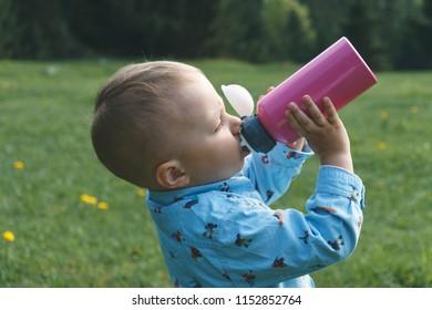 boy drinking water from bottle on meadow