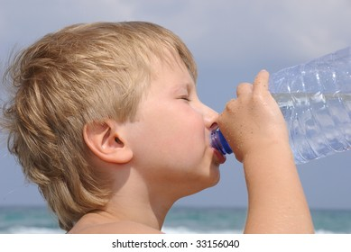 Boy drinking water from a bottle on a hot day