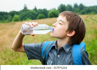 Boy drinking water from pet bottle outdoors