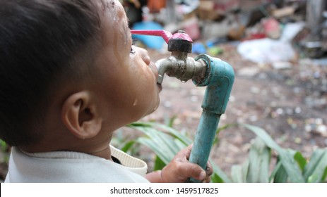 The boy is drinking water with thirst from the dirty water pipe, shooting blurred images