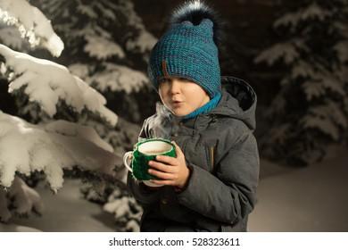 Boy drinks hot tea outdoor winter night among snow green trees