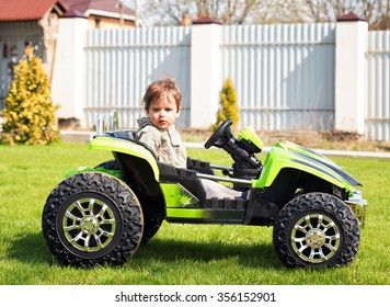 Boy drive electric mini car in the garden