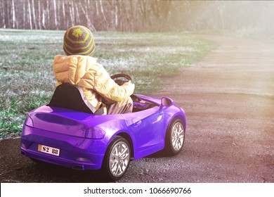 The boy is driving a blue car. A boy wearing a hat and jacket is playing with an electric toy car. Fun concept, children's day. Nice weather outside.