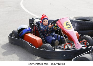 boy is driving Go-kart car with speed in a playground racing track.