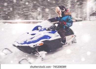Boy driving snowmobile in a winter landscape