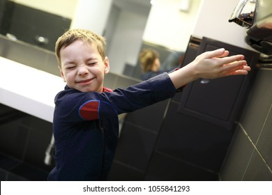 Boy drying his hands in a restroom
