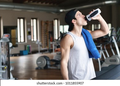 A boy during a break from training drinks from a water bottle or mineral supplement, as he has struggled a lot. Concept of: sports, gym, mineral salts and fitness