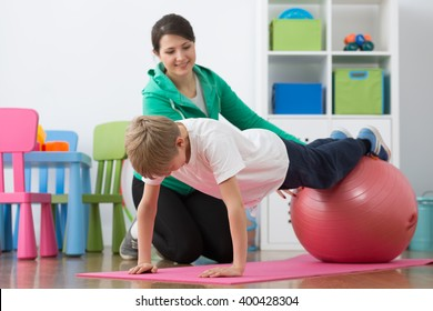 Boy during physiotherapy exercises on gym ball and woman instructor.