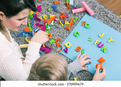 Boy during session with speech therapist learning letters