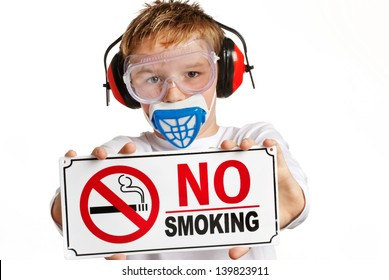 Boy with ear protection and face mask holding no smoking sign.